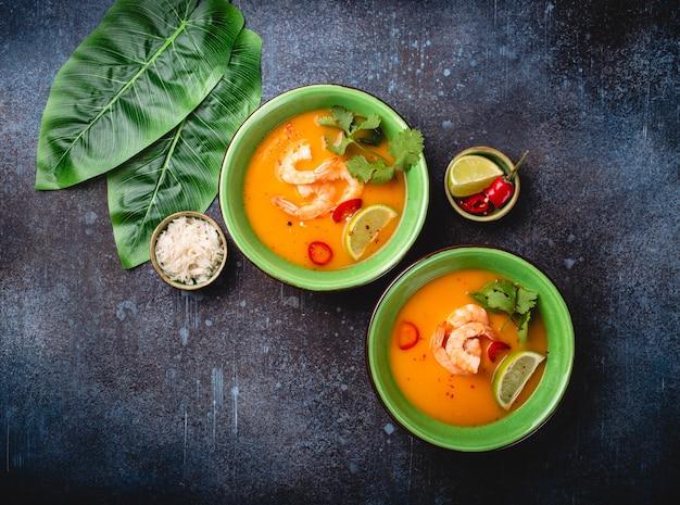 Традиционный здоровый тайский суп том ям с креветками, лаймом, кориандром в миске на деревенском фоне с белым рисом, накладной выстрел. аутентичная тайская кухня