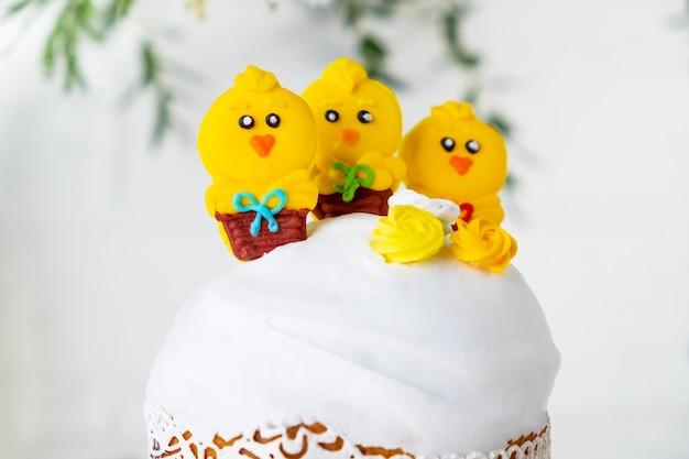 鶏で飾られた伝統的な休日のイースターケーキ白い背景のグリーティングカード
