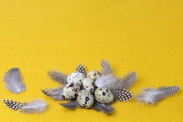 노란색 배경에 깃털의 둥지에 전통적인 휴일 회색, 갈색 메추라기 알,