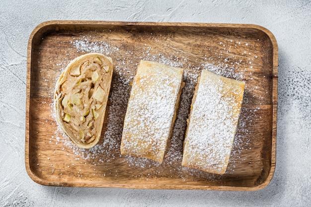 木製のトレイに伝統的な自家製のリンゴのシュトルーデル。白色の背景。上面図。