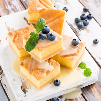Traditional homemade baked pudding cake with custard cream and blueberries
