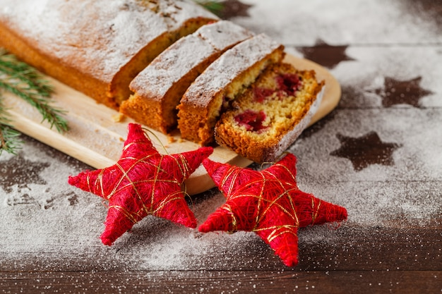 ヴィンテージの木製のテーブルに新年ツリー装飾フレームでクランベリーと伝統的な自家製クリスマスケーキデザート。素朴なスタイル。上面図