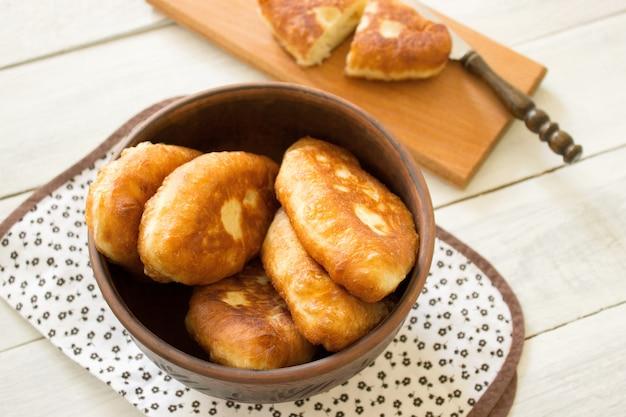 Традиционные домашние жареные пирожки или пироги в керамической миске. жареные русские пирожки из дрожжевого теста в деревенском стиле.