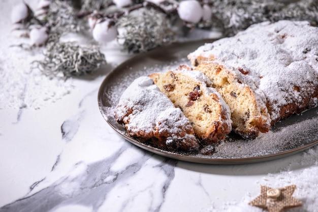 Традиционная домашняя немецкая рождественская выпечка хлеба для торта на тарелке с серебряными рождественскими украшениями на белом мраморном фоне