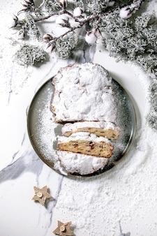 白い大理石の表面に銀のクリスマスの装飾が施されたプレート上の伝統的な自家製ドイツのクリスマスベーキングシュトーレンケーキパン。フラットレイ、スペース