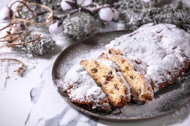 白い大理石の表面に銀のクリスマスの装飾が施されたプレート上の伝統的な自家製ドイツのクリスマスベーキングシュトーレンケーキパン。