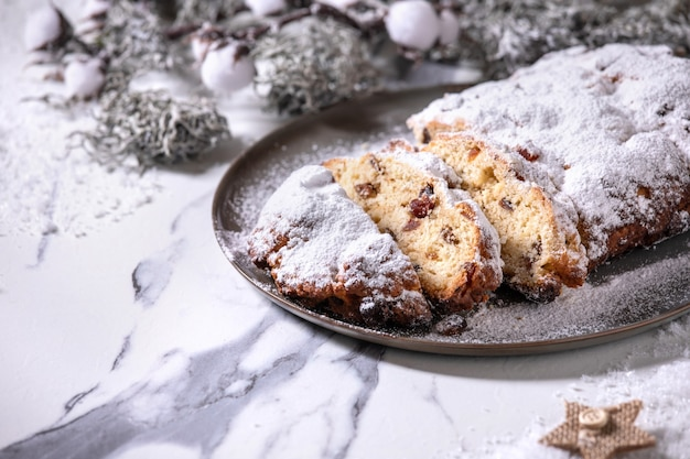 Traditional homemade german christmas baking stollen cake bread on plate with silver xmas decorations over white marble background