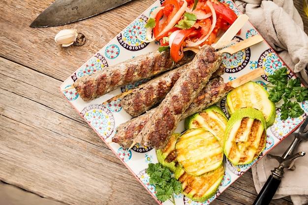 伝統的な自家製焼きトルコのアダナウルファケバブ、みじん切りの肉のケバブ、木の上にトマトサラダとズッキーニを添えたプレート