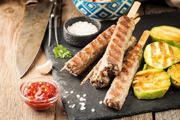 伝統的な自家製焼きトルコのアダナウルファケバブ、みじん切りの肉のケバブ、スレートプレートにトマトサラダとソースを添えて木製