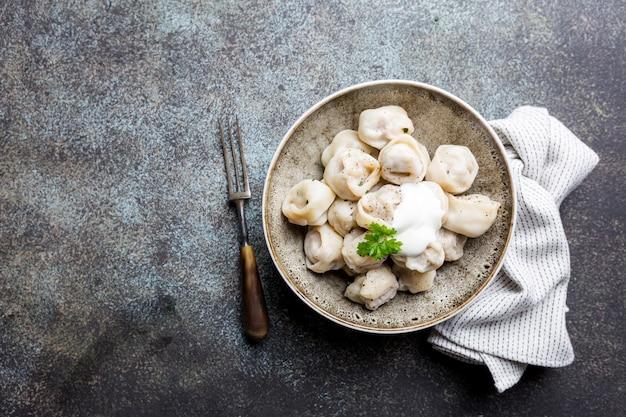 사워 크림과 회색 위에 채소를 곁들인 전통적인 수제 러시아 pelmeni 고기 만두.
