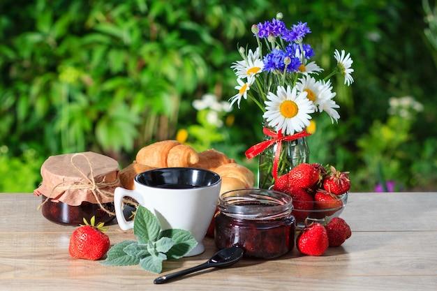 緑のぼやけた自然の背景を持つ木製のテーブルに新鮮なイチゴ、クロワッサン、カモミールで飾られた瓶の伝統的な自家製イチゴジャム