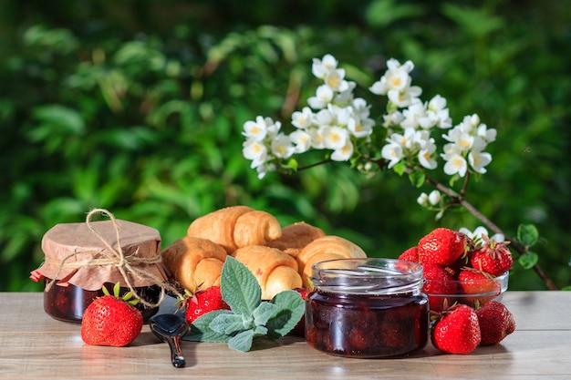 緑のぼやけた自然の背景を持つ木製のテーブルに新鮮なイチゴ、クロワッサン、ジャスミンで飾られた瓶の伝統的な自家製イチゴジャム