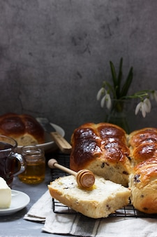 Traditional hot cross buns with honey and butter on a concrete surface