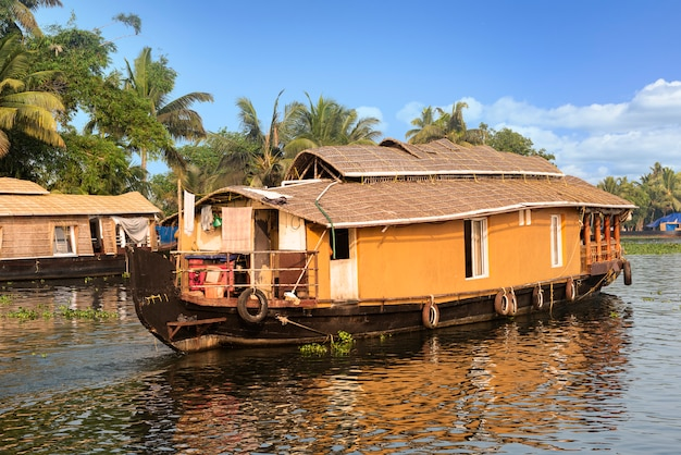 Traditional house boat is anchored on the shores of a fishing lake in india.