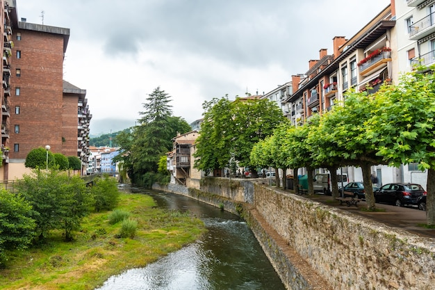 Traditional houses in the town of azkoitia next to the urola river and church of santa marãa la real in the background, gipuzkoa. basque country