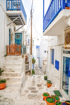 Traditional houses with blue doors and windows in the narrow streets of greek village in mykonos, greece