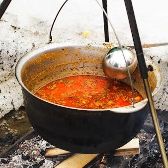 Традиционное венгерское блюдо - гуляш бограц, тушеное мясо и овощи в казане, на улице в зимнем камине.