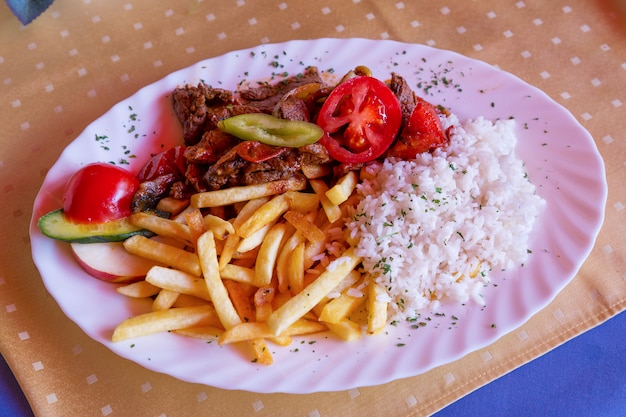 Traditional hungarian goulash with rice, french fries and pepper close up