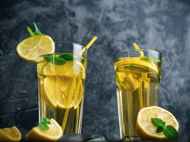 Traditional iced, lemon and mint iced tea . mojito in two glass glasses on a dark concrete table