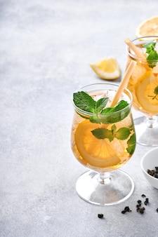 大理石のテーブルの背景に背の高いグラスにレモンと氷の伝統的なアイスティーレモンとアイスティー。セレクティブフォーカス。さわやかな冷たい夏の飲み物。