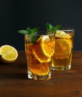 背の高いグラスの夏の飲み物にレモンと氷を入れた伝統的なアイスティー