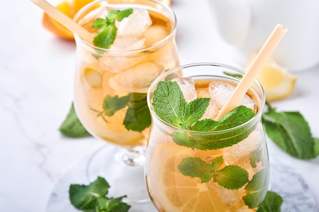 Traditional iced tea with lemon and ice in tall glasses on marble table background iced tea with lemon. selective focus. refreshment cold summer drink.