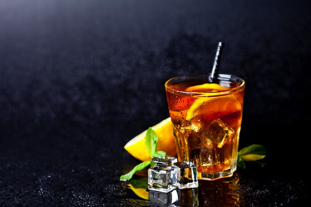 Traditional iced tea with lemon, mint leaves and ice cubes in glass on wet black background.