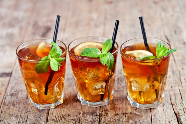 Traditional iced tea with lemon, mint leaves and ice cubes in glasses on rustic wooden table.
