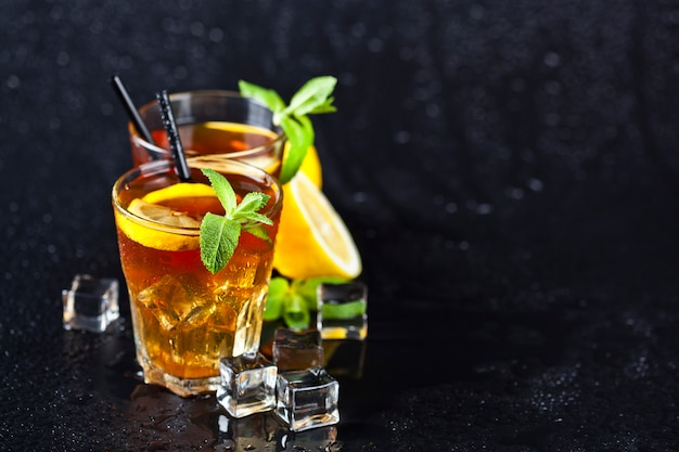 Traditional iced tea with lemon, mint leaves and ice cubes in two glasses on wet black background.