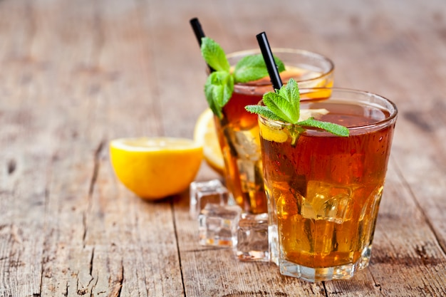 Traditional iced tea with lemon, mint leaves and ice cubes in two glasses