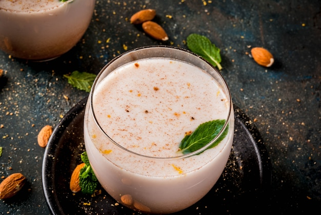 Traditional indian beverage, holi festival food, thandai sardai milk drink with nuts, spices, mint. dark blue background, copy space