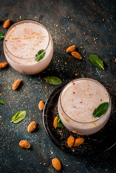 Traditional indian beverage, holi festival food, thandai sardai milk drink with nuts, spices, mint.