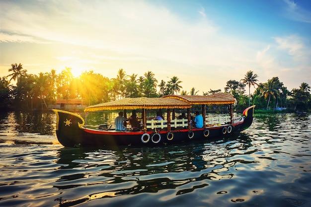 Традиционная индийская лодка. керала, туристы отдыхают на лодке вечером на фоне красивого заката и природы пальм. речной трамвай перевозит пассажиров по каналам аллеппи.