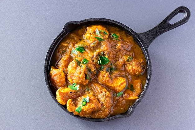 Traditional indian butter chicken curry and lemon served iron-cast. top view. traditional world cuisine.
