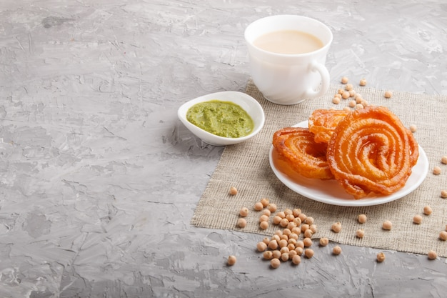 Traditional indian candy jalebi in white plate with mint chutney on a gray concrete copyspace. side view.