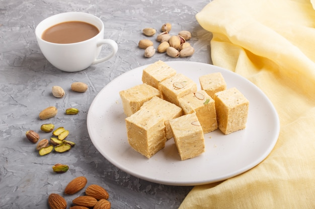 Traditional indian candy soan papdi in white plate with almond and pistache on a gray concrete.