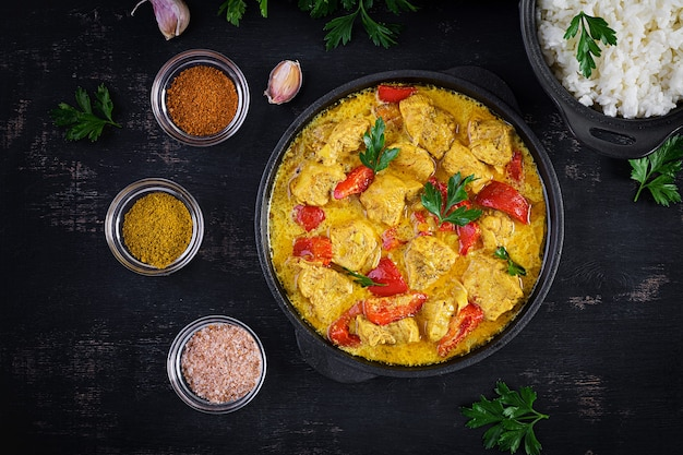 Traditional indian curry chicken masala. indian chicken curry with sweet peppers and  rice in bowl, spices, dark background. traditional indian dish. top view, flat lay