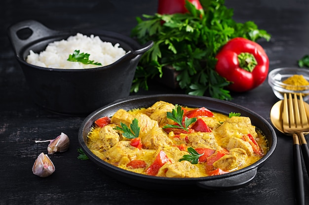 Traditional indian curry chicken masala. indian chicken curry with sweet peppers and  rice in bowl, spices, dark background. traditional indian dish.