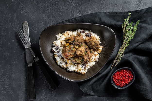 Traditional indian curry lamb meat masala.  black background.