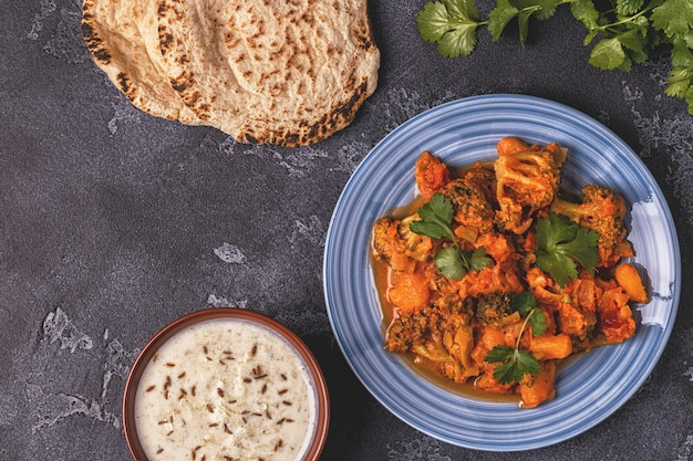 Traditional indian curry with vegetables and bread raita