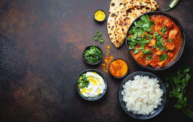 テキスト用のスペースがある伝統的なインド料理チキンティッカマサラ。ボウルにスパイシーなカレー肉、バスマティライス、パンナン、素朴な暗い背景にヨーグルトライタソース、上面図、クローズアップ、コピースペース