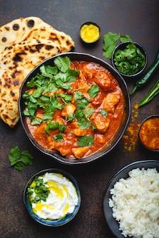 伝統的なインド料理チキンティッカマサラとスパイシーなカレー肉のボウル、バスマティライス、パンナーン、素朴な暗い背景のヨーグルトライタソース、上面図、クローズアップ。上からのインド風ディナー