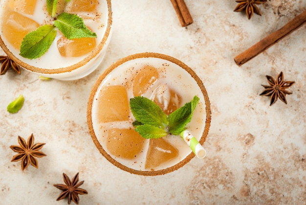 Traditional indian drink is iced tea or chai masala, with ice cubes from chai, milk and mint leaves. with striped straws. on light beige stone table.  top view