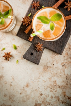 Traditional indian drink is iced tea or chai masala with ice cubes from chai milk and mint leaves. with striped straws on a wooden board. on light beige stone table