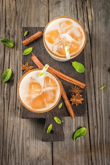 Traditional indian drink is iced tea or chai masala, with ice cubes from chai, milk and mint leaves. with striped straws, on a wooden board. on an old rustic wooden table. copy space top view