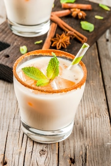 Traditional indian drink is iced tea or chai masala, with ice cubes from chai, milk and mint leaves. with striped straws, on a wooden board. on an old rustic wooden table. copy space