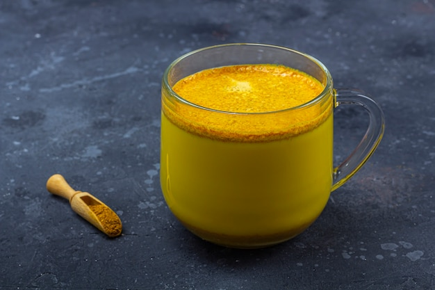 Traditional indian drink turmeric milk is golden milk in glass mug with cinnamon, anis star, turmeric on dark background. weight loss, healthy and organic drink