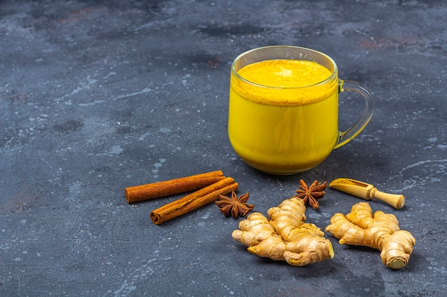 Traditional indian drink turmeric milk is golden milk in glass mug with  turmeric and root ginger, cinnamon, anis star