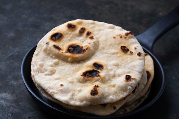 伝統的なインドのフラットブレッドチャパティ。鋳鉄フライパンで簡単な家庭料理のコンセプト。閉じる。