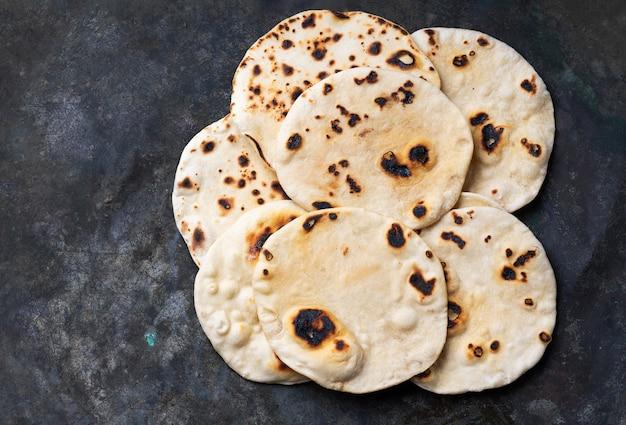 素朴なテーブルの上に伝統的なインドのフラットブレッドチャパティ。簡単な家庭料理のコンセプト。上面図。フラットレイ。